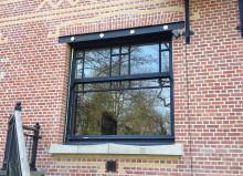 houten raam met donkere moluren